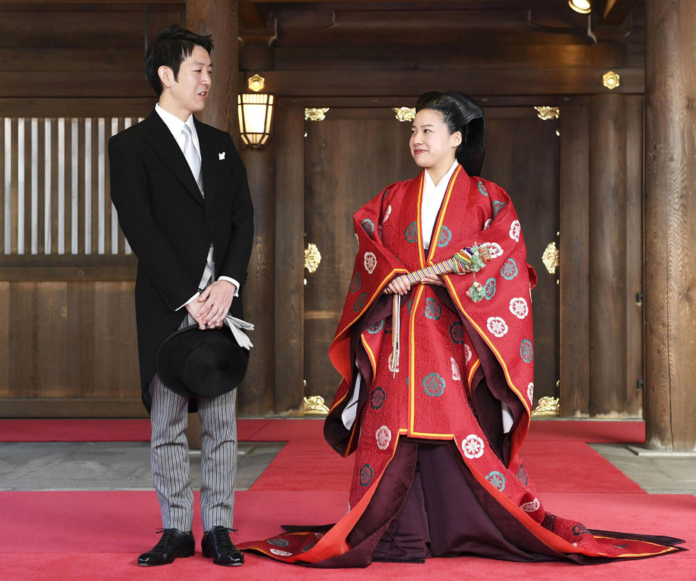 Princess Ayako, right, dressed in a traditional ceremonial robe, and groom Kei Moriya speak to reporters after their wedding ceremony at the Meiji Shrine in Tokyo, on Monday, Oct. 29, 2018. The daughter of the emperor's cousin married the commoner in a ritual-filled ceremony. (Kyodo News via AP)