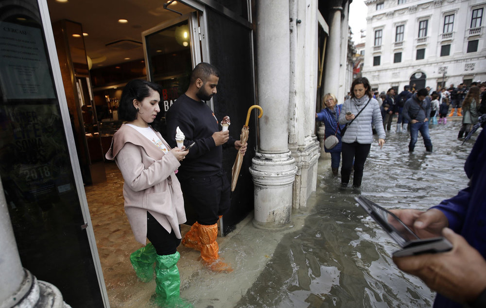Tourists check their smartphones as they stroll through a flooded St. Mark's Square in Venice, Italy, Thursday, Nov. 1, 2018. Two people were killed when a falling tree crushed their car in the mountainous countryside in northwestern Italy, as rainstorms and strong winds struck much of the nation. (AP Photo/Luca Bruno)