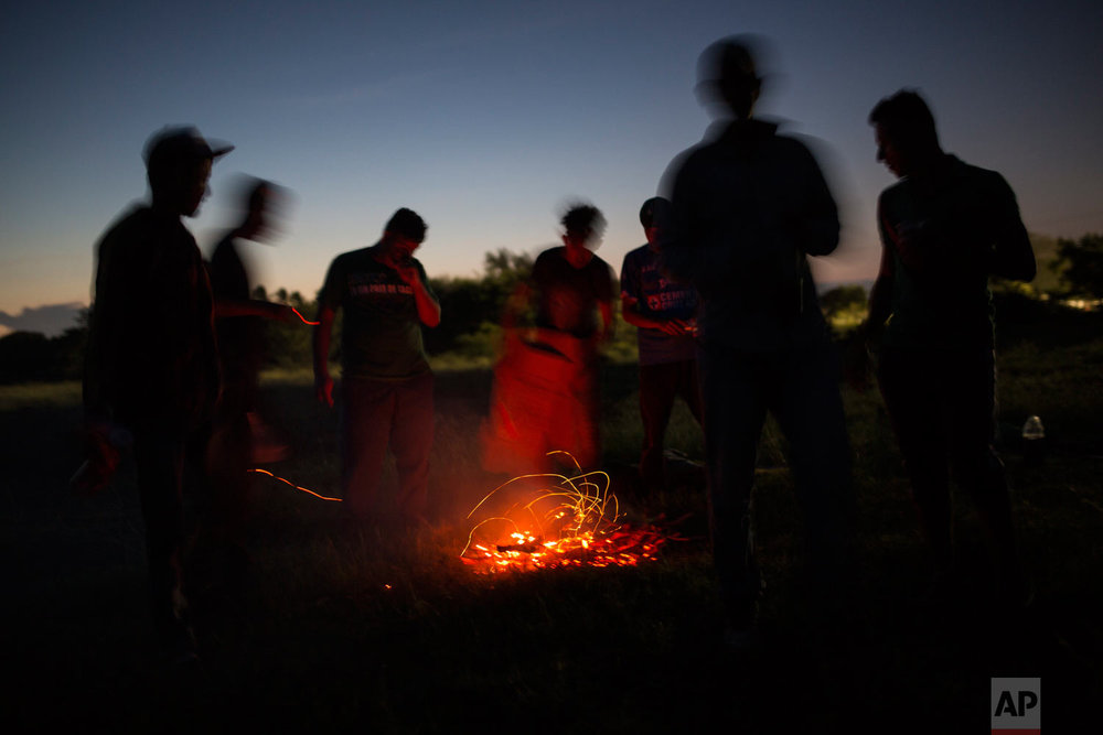 Central American migrants gather around a fire at a camp set up by a caravan of thousands of migrants, in Juchitan, Mexico, after sunset Tuesday, Oct. 30, 2018. This caravan of about 4,000 mainly Honduran migrants set up camp Tuesday in the Oaxaca state city of Juchitan, which was devastated by an earthquake in September 2017. (AP Photo/Rodrigo Abd)