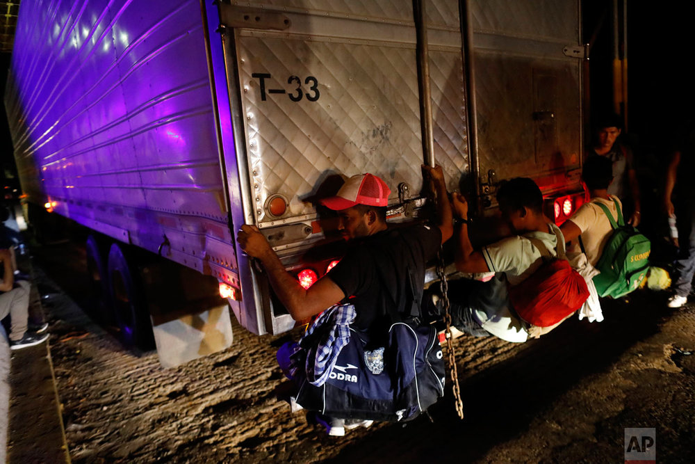 Central Americans cling to the back of a truck as a thousands-strong migrant caravan slowly heads north in hopes of reaching the U.S. border, between Pijijiapan and Tonala, Chiapas state, Mexico, before dawn on Friday, Oct. 26, 2018. Many migrants said they felt safer traveling and sleeping with several thousand strangers in unknown towns than hiring a smuggler or trying to make the trip alone. (AP Photo/Rebecca Blackwell)