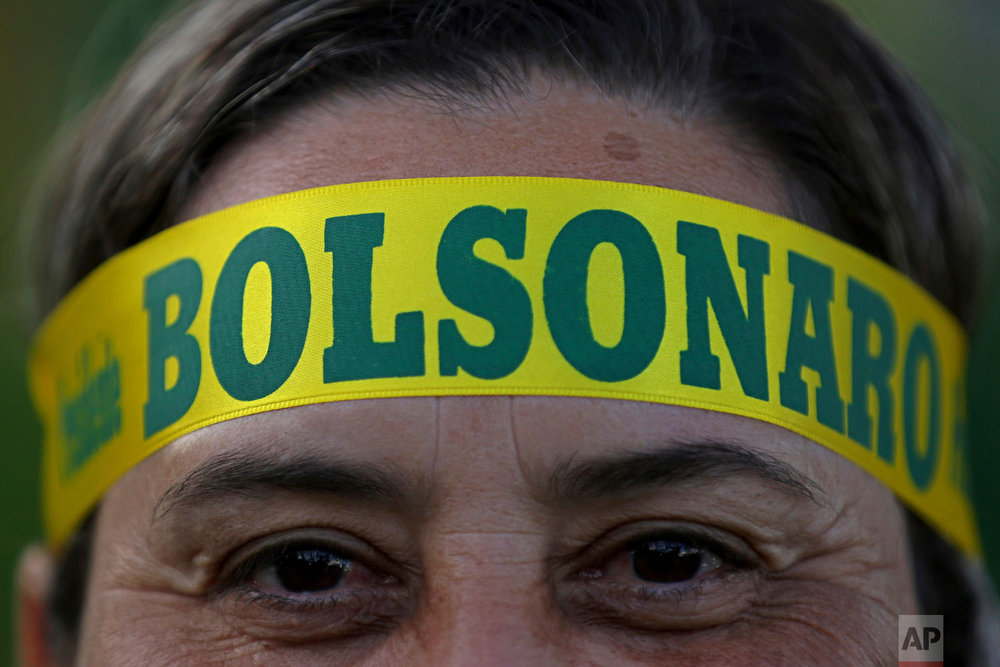 A supporter of presidential front-runner Jair Bolsonaro wears a headband supporting his candidate as he waits with others for election results outside the National Congress in Brasilia, Brazil, Oct. 28, 2018. Brazilian voters decide who will next lead the world's fifth-largest country, the left-leaning Fernando Haddad of the Workers' Party, or right-leaning rival Bolsonaro of the Social Liberal Party. (AP Photo/Eraldo Peres)