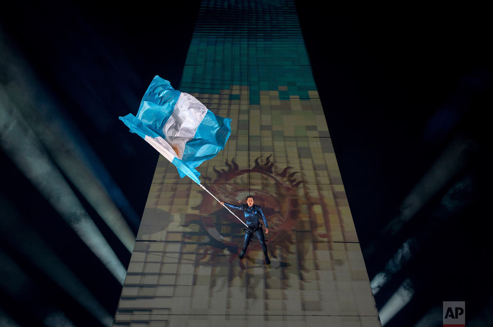 In this photo provided by the OIS/IOC, a performer repelling from the Obelisk of Buenos Aires holds the Argentine national flag at the start of the Youth Olympic Summer Games opening ceremony, in Buenos Aires, Argentina, Oct. 6, 2018. Over 4,000 of the world's best young athletes between the ages of 15 to 18 are in the Argentinian capital for the third edition of the Youth Olympic Summer Games, the first time in Olympic history that an equal number of male and female athletes are competing in the youth games.(Florian Eisele/OIS/IOC via AP)