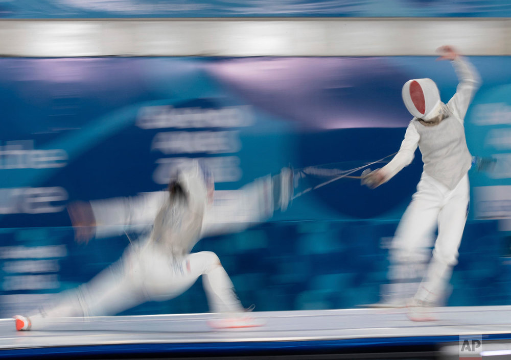 In this photo provided by the OIS/IOC, USA's May Tieu, left, and France's Venissia Thepaut compete in a mixed continental fencing team match during the Youth Olympic Summer Games in Buenos Aires, Argentina, Oct. 10, 2018. (Ian Walton /OIS/IOC via AP)