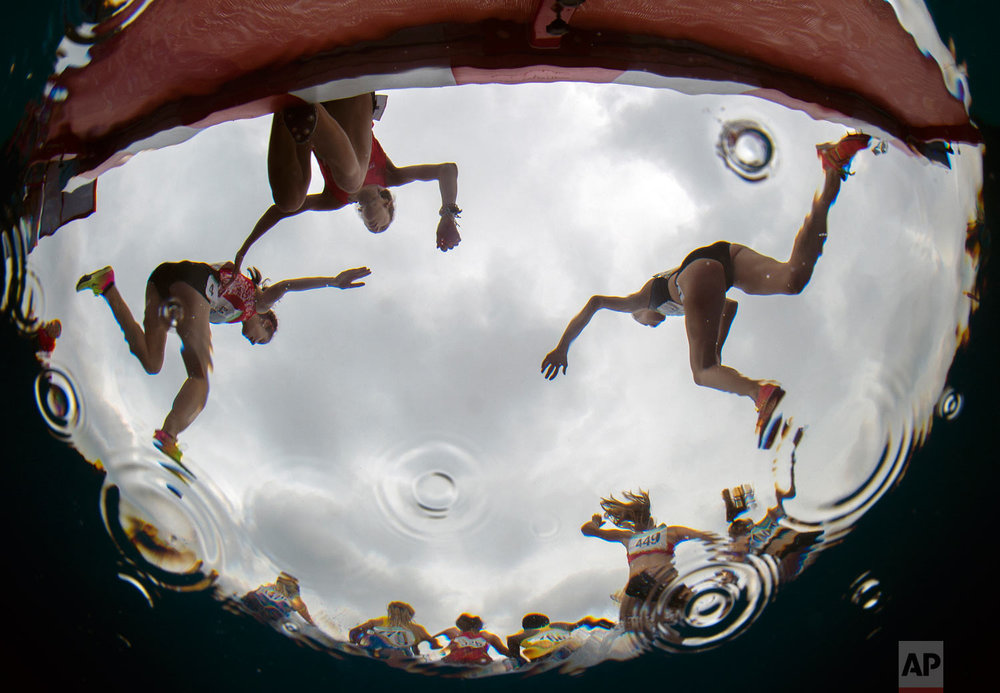 In this photo provided by the OIS/IOC, athletes are reflected in water during the Women's Athletics 3000m during the Youth Olympic Games in Buenos Aires, Argentina, Oct. 12, 2018. (Joel Marklund/OIS/IOC via AP)