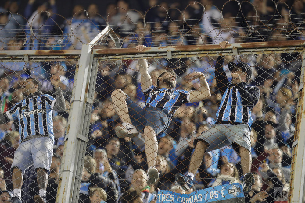 Fans of Brazil's Gremio celebrate on the fence after Michel's goal against Argentina's River Plate during a Copa Libertadores semifinal first leg soccer match in Buenos Aires, Argentina, Oct. 23, 2018. Gremio won 1-0. (AP Photo/Natacha Pisarenko)