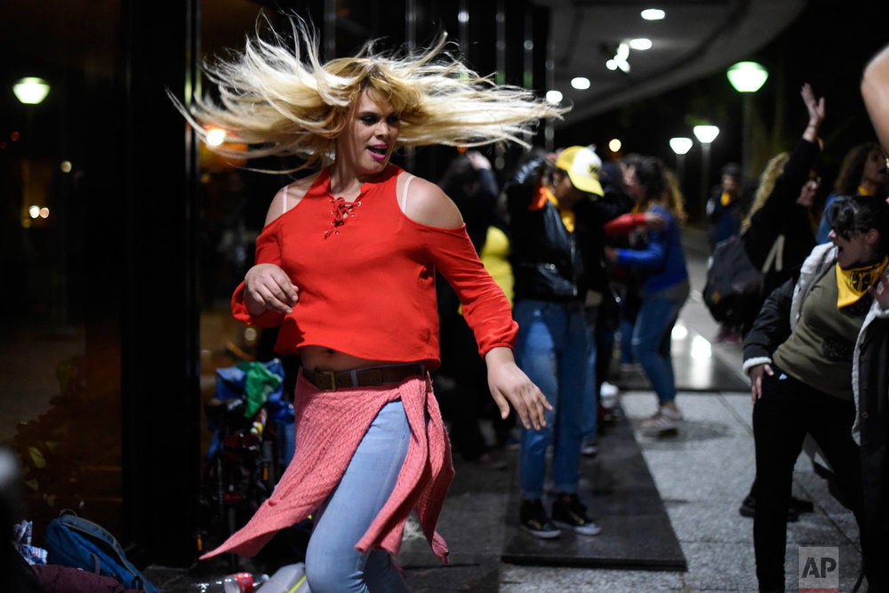 Activists dance to celebrate outside the Legislative Palace after the approval of the Integral Law for Trans People that was passed by legislators in Montevideo, Uruguay, Oct. 19, 2018. The law grants transgender people the right to get an operation that matches their sexual identity and be paid for by the state along with hormone treatments. (AP Photo/Matilde Campodonico)