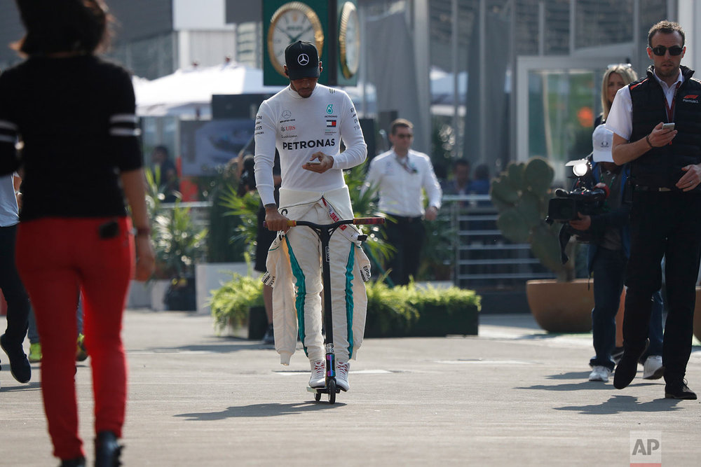 Mercedes driver Lewis Hamilton, of Britain, rides a scooter to the pit lane ahead of the first training session of the Formula One Mexico Grand Prix auto race at the Hermanos Rodriguez racetrack in Mexico City, Oct. 26, 2018. (AP Photo/Moises Castillo)
