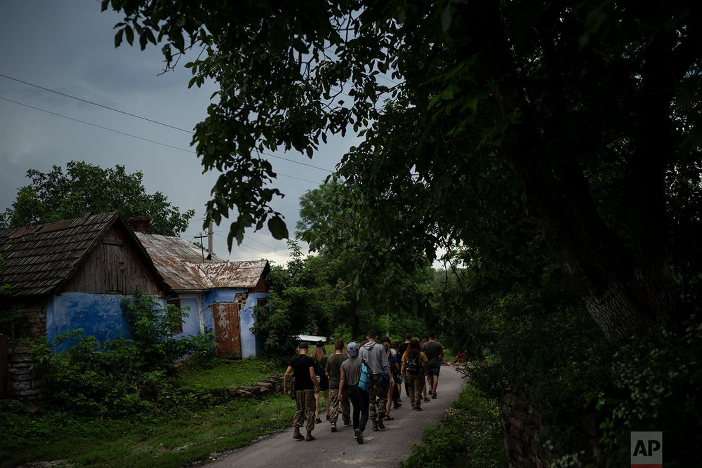 "Young participants of the ""Temper of will"" summer camp, organized by the nationalist Svoboda party, walk to a campsite on July 27, 2018, in a village near Ternopil, Ukraine. (AP Photo/Felipe Dana)"