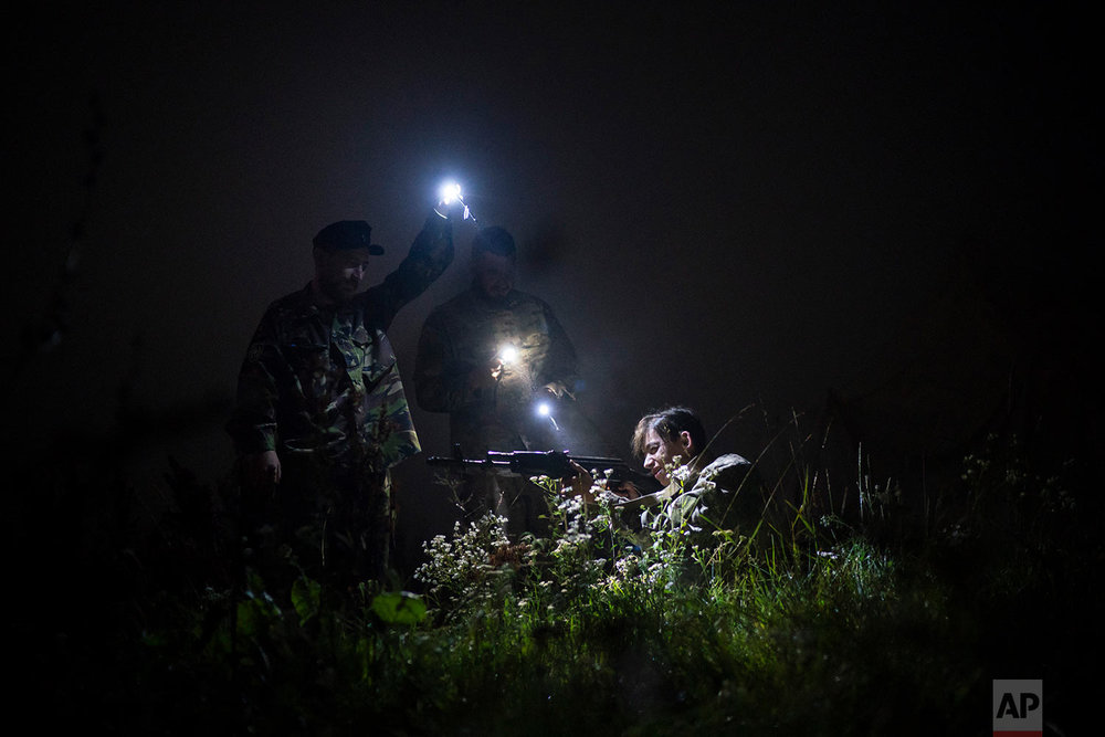 "Yuri Chornota Cherkashin, head of Sokil, left, and instructor Georgiy Barylenko, center, point flashlights on a young participant of the ""Temper of will"" summer camp, organized by Svoboda party during a night drill on July 29, 2018, in a village near Ternopil, Ukraine. (AP Photo/Felipe Dana)"