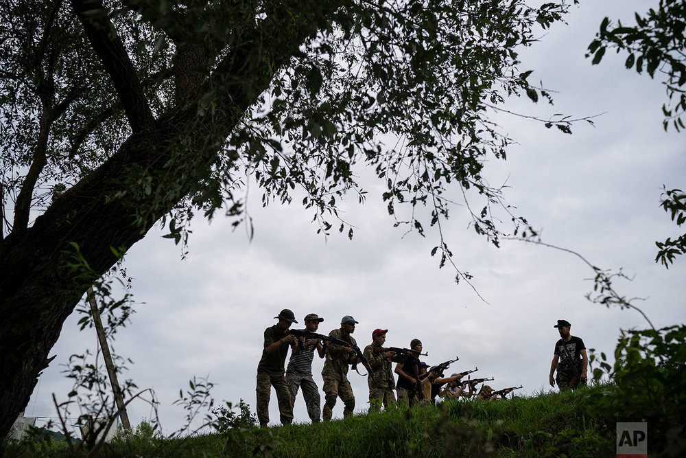 "Yuri Chornota Cherkashin, right, head of Sokil, gives tactical instructions to young participants of the ""Temper of will"" summer camp, organized by Svoboda party on July 29, 2018, in a village near Ternopil, Ukraine. (AP Photo/Felipe Dana)"