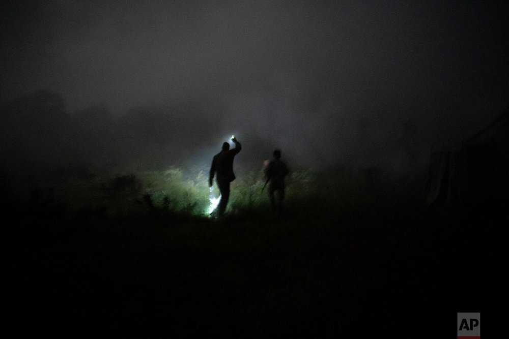 "Instructor Georgiy Barylenko, left, holds a flashlight as he walks with a young participant of the ""Temper of will"" summer camp, organized by the nationalist Svoboda party, during a night drill on July 29, 2018, in a village near Ternopil, Ukraine. (AP Photo/Felipe Dana)"