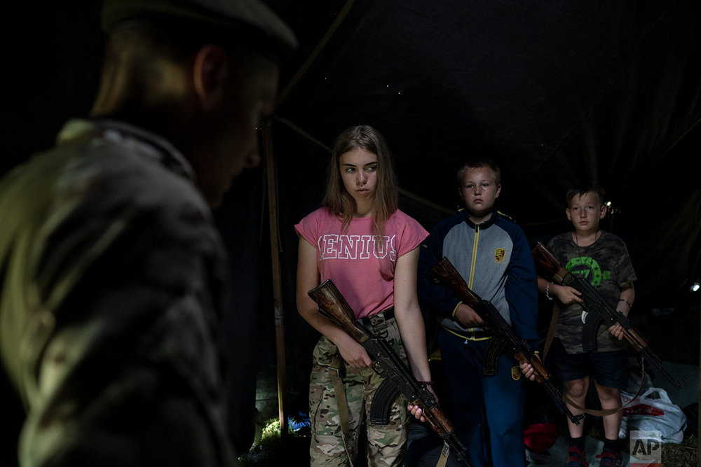 "Participants of the ""Temper of will"" summer camp, organized by the nationalist Svoboda party, hold their AK-47 riffles as they receive instructions during a tactical exercise on July 28, 2018, in a village near Ternopil, Ukraine. Campers as young as 8 years old practice using assault rifles. They are taught to shoot to kill Russians and their sympathizers. (AP Photo/Felipe Dana)"