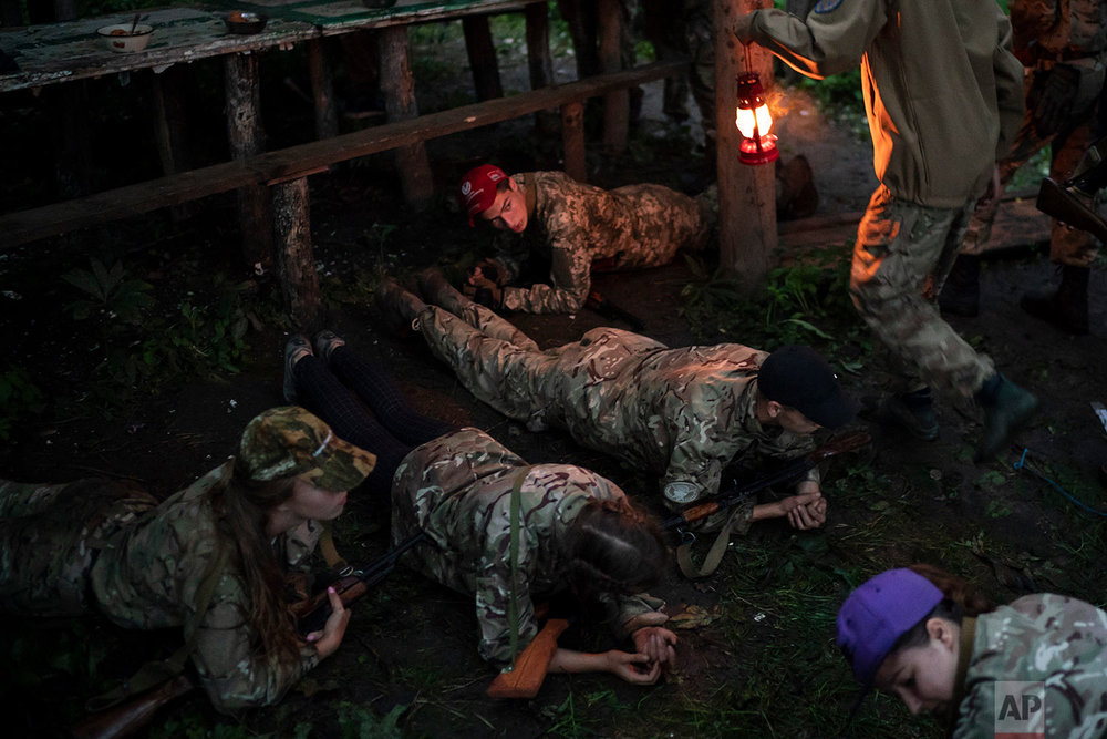 "Young participants of the ""Temper of will"" summer camp, organized by the nationalist Svoboda party, hold a plank position before having dinner on July 28, 2018, in a village near Ternopil, Ukraine. (AP Photo/Felipe Dana)"