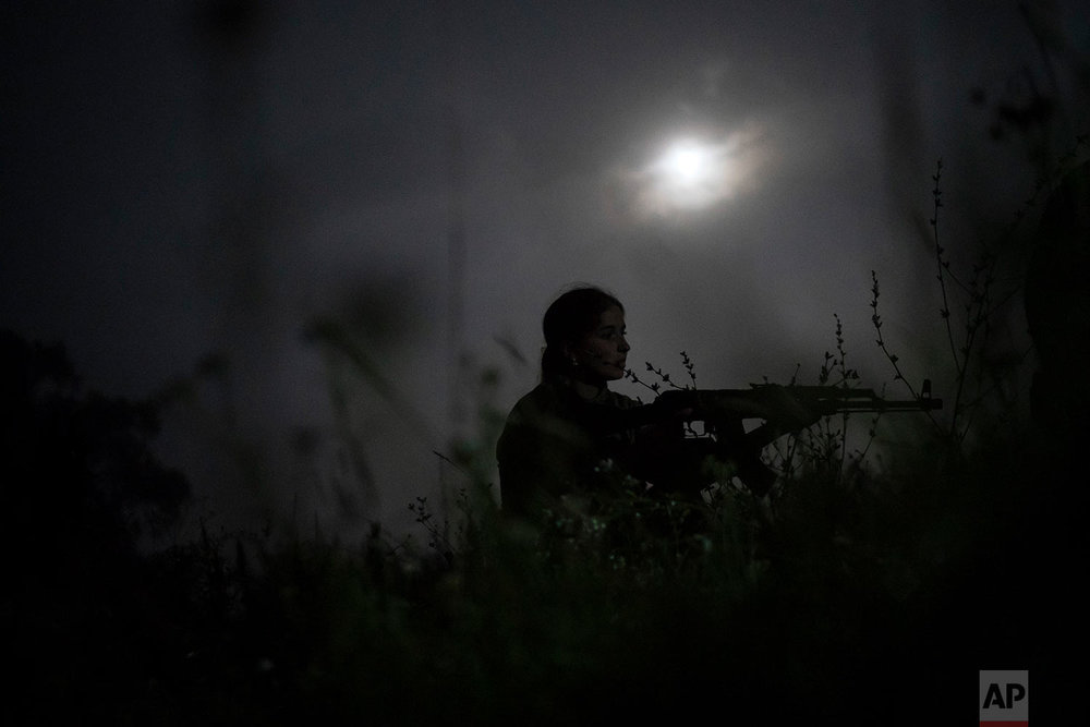 "A young participant of the ""Temper of will"" summer camp, organized by the nationalist Svoboda party, takes position with her unloaded AK-47 riffle during a night exercise on July 29, 2018, in a village near Ternopil, Ukraine. (AP Photo/Felipe Dana)"