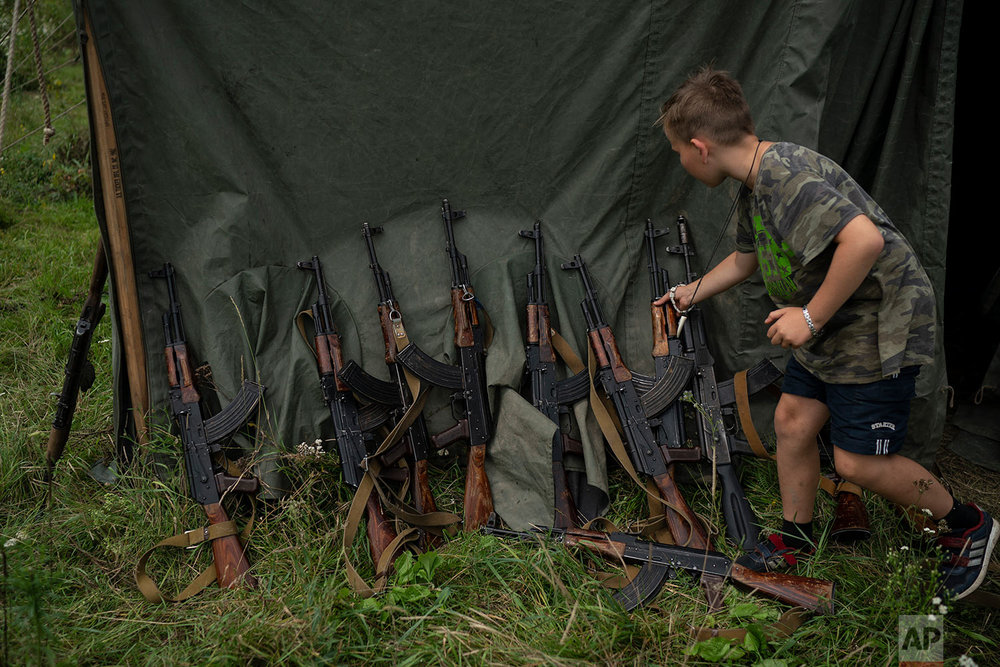 "A young participant of the ""Temper of will"" summer camp, organized by the nationalist Svoboda party, grabs his AK-47 during a tactical exercise on July 28, 2018, in a village near Ternopil, Ukraine. ""We never aim guns at people,"" instructor Yuri ""Chornota"" Cherkashin tells campers. ""But we don't count separatists, little green men, occupiers from Moscow as people, so we can and should aim at them."" (AP Photo/Felipe Dana)"