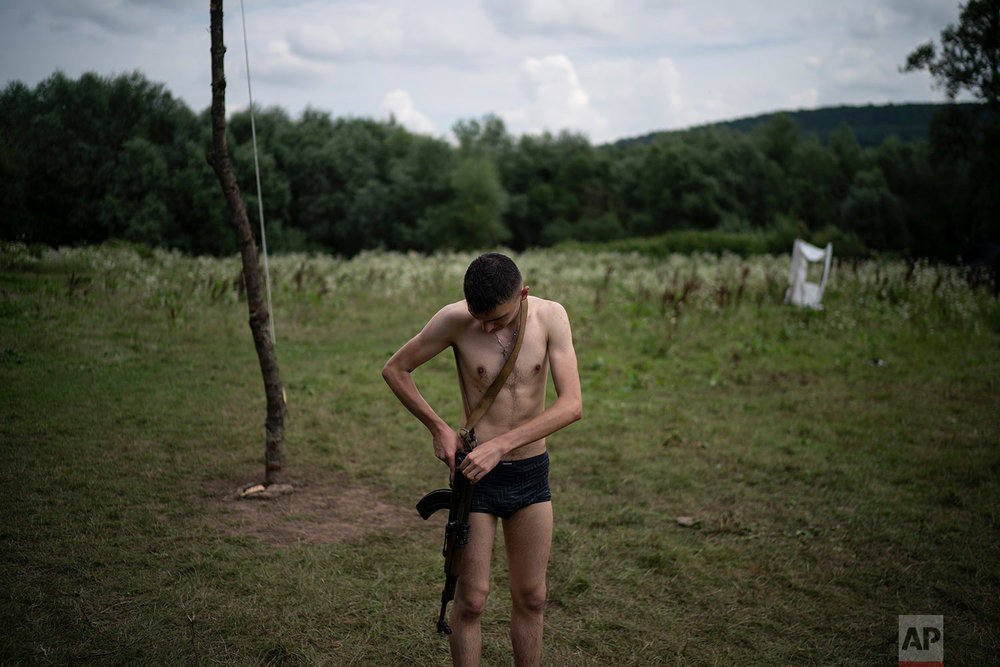 "Mykhailo adjusts his AK-47 riffle after bathing in a river during the ""Temper of will"" summer camp, organized by the nationalist Svoboda party on July 29, 2018, in a village near Ternopil, Ukraine. At 18, he is the oldest of the campers. ""Every moment things can go wrong in our country. And one has to be ready for it,"" he said. ""That's why I came to this camp. To study how to protect myself and my loved ones."" (AP Photo/Felipe Dana)"