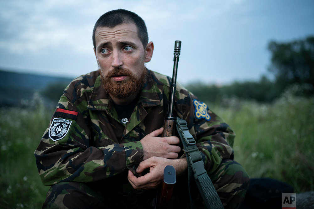 "Yuri ""Chornota"" Cherkashin, head of Sokil (Falcon), the youth wing of the nationalist Svoboda party, sits with his AK-47 rifle at the ""Temper of will"" summer camp on July 29, 2018, in a village near Ternopil, Ukraine. ""We never aim guns at people,"" he tells his campers. ""But we don't count separatists, little green men, occupiers from Moscow as people, so we can and should aim at them."" (AP Photo/Felipe Dana)"