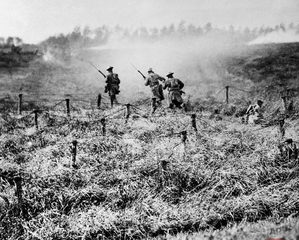 In this Sept. 13, 1918 photo, U.S. troops of the 107th Regiment Infantry, 27th Division, advance on a path through a barbed wire entanglement near Beauqueanes, Somme, France during World War One. (AP Photo/U.S. Army Signal Corps)