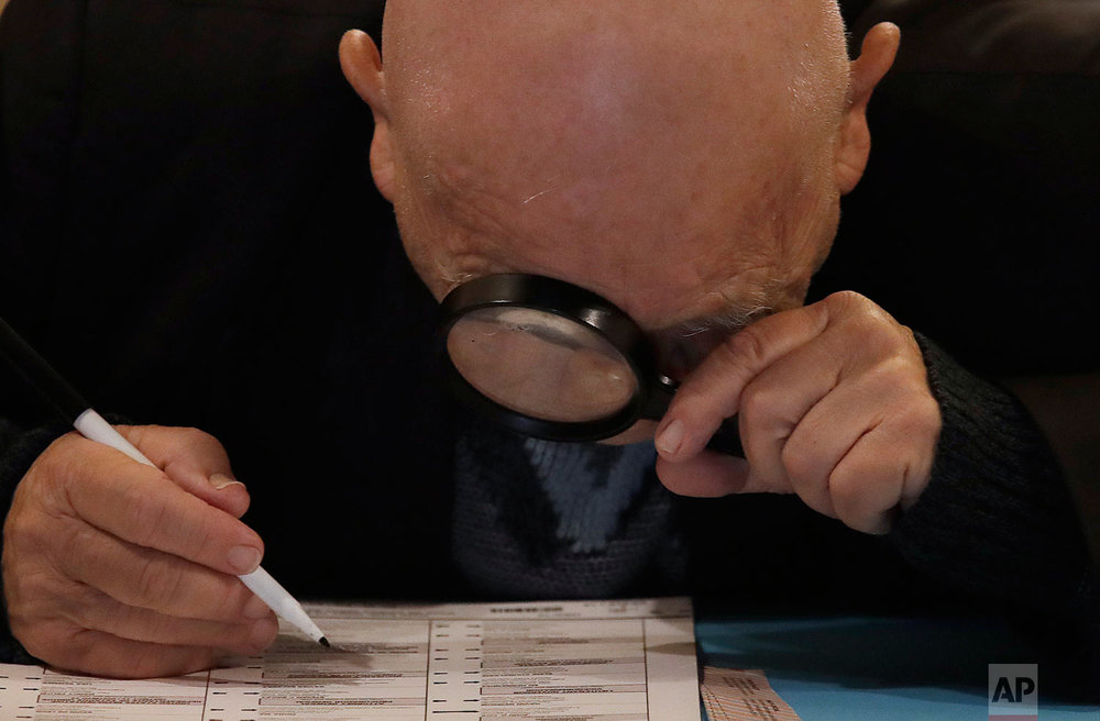 Yuriy Glukhoy, originally from Russia, looks through a magnifying glass as he marks his ballot to vote at the San Francisco Columbarium & Funeral Home in San Francisco on Tuesday, Nov. 6, 2018. Built in 1898, the columbarium is one of the last remaining cemeteries in San Francisco. (AP Photo/Jeff Chiu)
