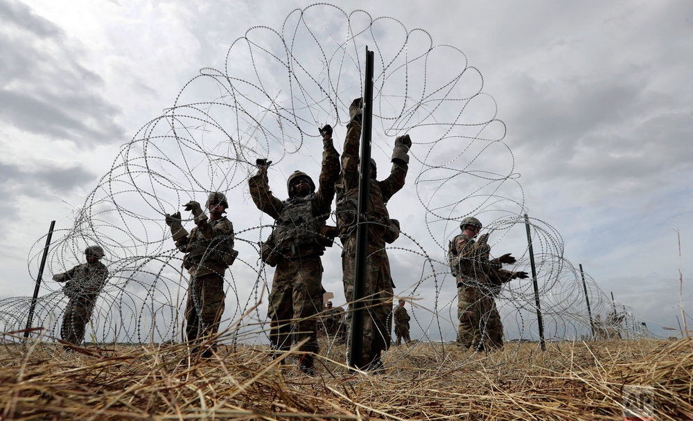 Members of a U.S Army engineering brigade place concertina wire around an encampment for troops, and personnel from the Department of Defense and U.S. Customs and Border Protection near the U.S.-Mexico International bridge, Sunday, Nov. 4, 2018, in Donna, Texas. (AP Photo/Eric Gay)
