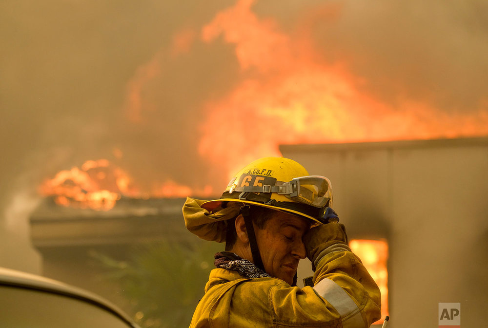A firefighter keeps watch as the wildfire burns a home near Malibu Lake in Malibu, Calif., Nov. 9, 2018. (AP Photo/Ringo H.W. Chiu)