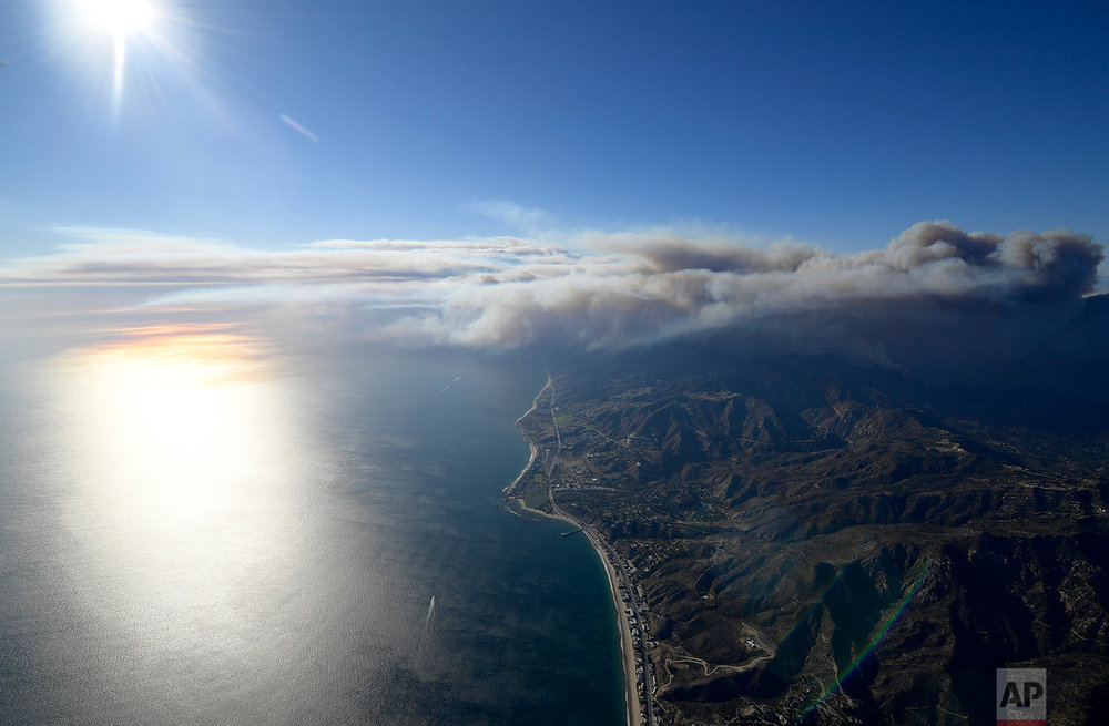 Fires burn toward the pacific ocean as seen Friday, Nov. 9, 2018, from a helicopter over Santa Monica, Calif. (AP Photo/Mark J. Terrill)