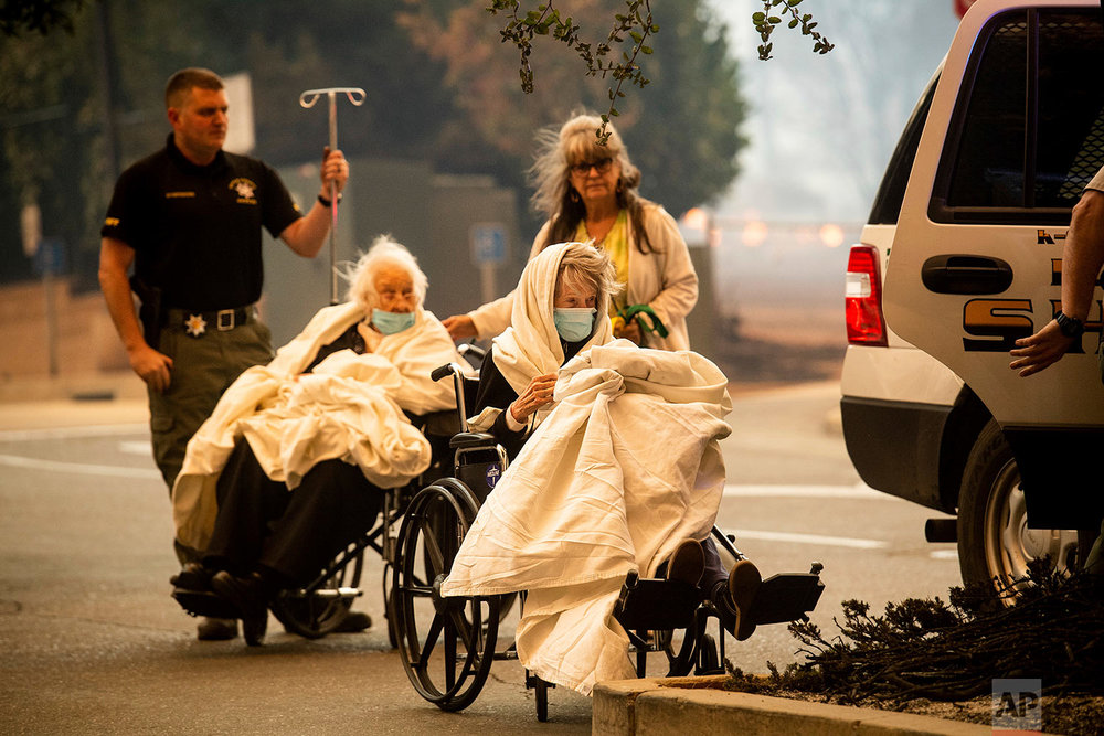 Emergency personnel evacuate patients as the Feather River Hospital burns while the Camp Fire rages through Paradise, Calif., on Thursday, Nov. 8, 2018. (AP Photo/Noah Berger)