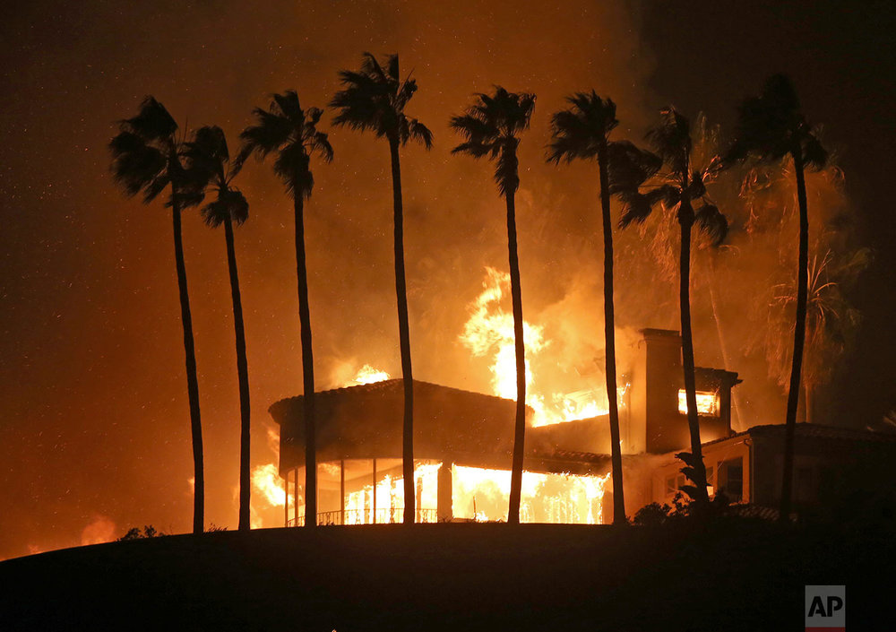 Palm trees frame a home being destroyed by a wildfire above Pacific Coast Highway in Malibu, Calif., Friday, Nov. 9, 2018. (AP Photo/Reed Saxon)