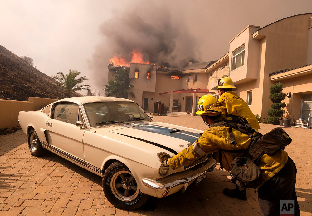 Firefighters push a vehicle from a garage as the Woolsey fire burning a home near Malibu Lake in Malibu, Calif., Friday, Nov. 9, 2018. (AP Photo/Ringo H.W. Chiu)