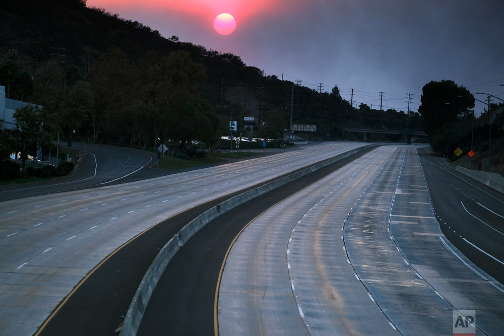The sun sets through the smoke of a wildfire burning behind Highway 101 closed in both directions outside of Calabasas, Calif., on Friday, Nov. 9, 2018. (AP Photo/Richard Vogel)
