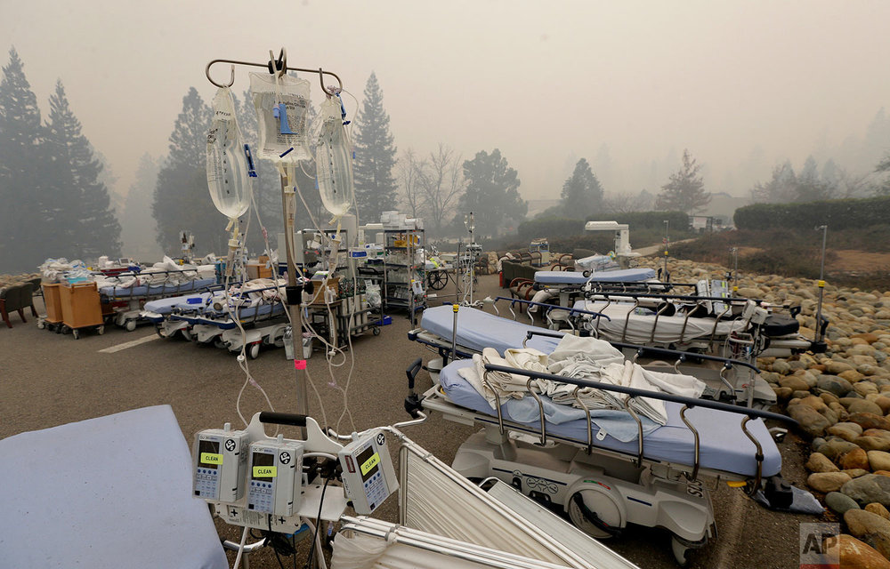 Hospital beds and other equipment sit in a parking lot outside the Feather River Hospital Friday, Nov. 9, 2018, in Paradise, Calif. Patients were evacuated from the hospital before a massive wildfire swept through the area, Thursday. One building was burned in the fire, but firefighters were able to stop the blaze before it did more damage. (AP Photo/Rich Pedroncelli)