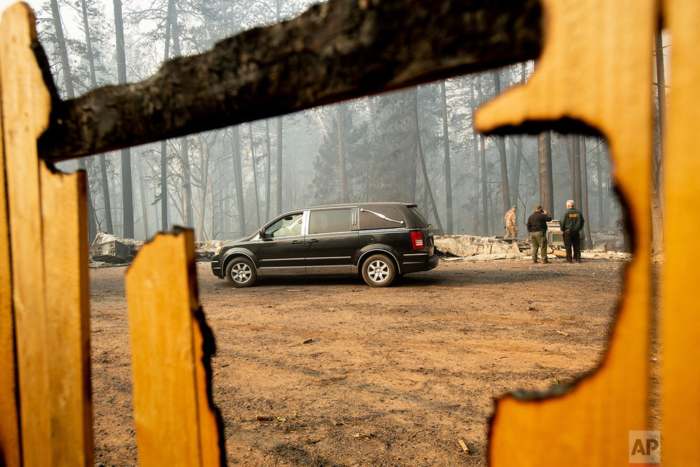 Sheriff's deputies search for human remains at a residence destroyed by the Camp Fire on Saturday, Nov. 10, 2018, in Paradise, Calif. The hearse carries multiple victims. (AP Photo/Noah Berger)