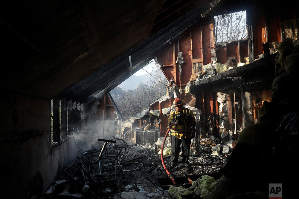 Capt. Adrian Murrieta with the Los Angeles County Fire Dept., looks for hot spots on a wildfire-ravaged home Saturday, Nov. 10, 2018, in Malibu, Calif. (AP Photo/Marcio Jose Sanchez)