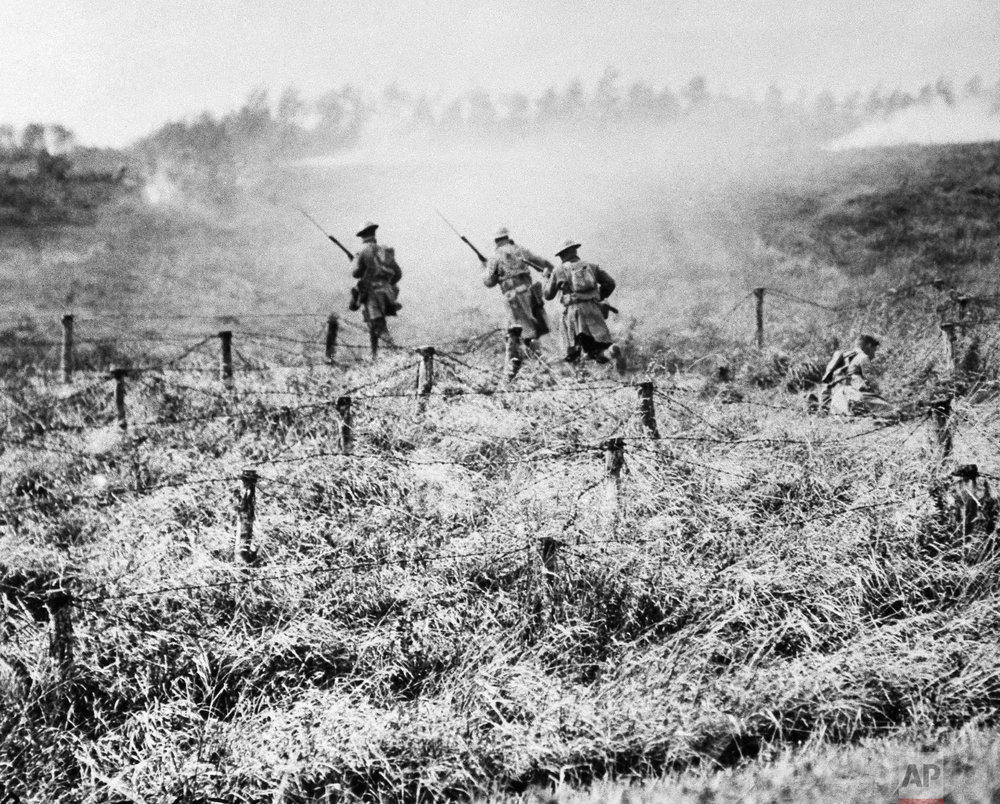 U.S. troops of the 107th Regiment Infantry, 27th Division, advance on a path through a barbed wire entanglement near Beauqueanes, Somme, France during World War One on Sept. 13, 1918. (AP Photo/U.S. Army Signal Corps)