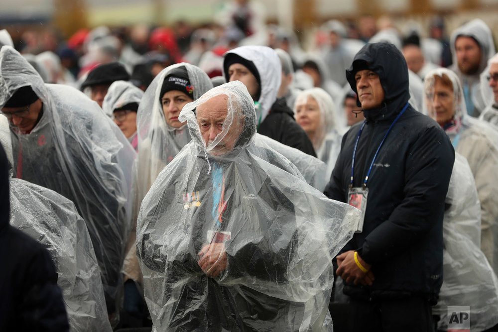 People observe a minute of silence as it rains during an Armistice ceremony at the World War I Australian National Memorial in Villers-Bretonneux, France, Nov. 11, 2018. (AP Photo/Francisco Seco)
