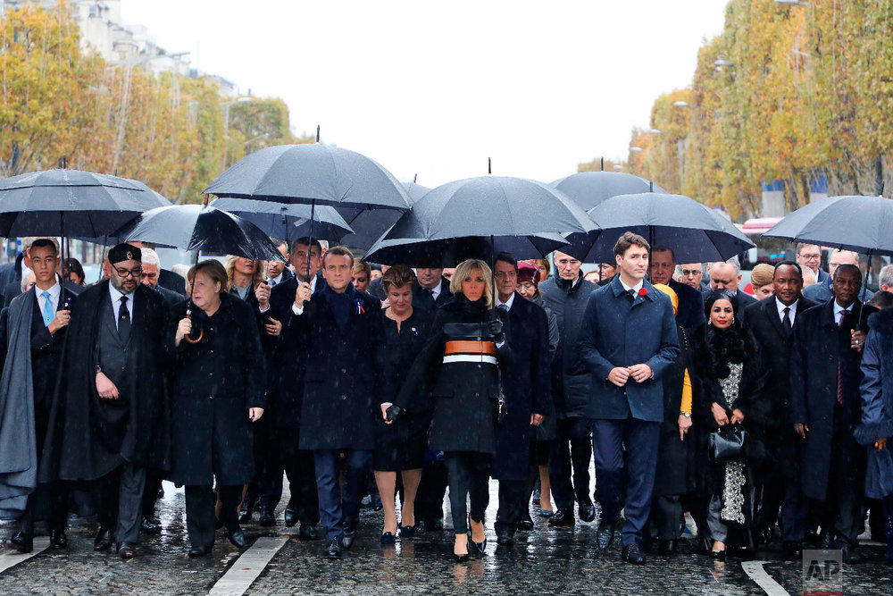 Morocco's Prince Moulay Hassan, from left, Moroccan King Mohammed VI, German Chancellor Angela Merkel, French President Emmanuel Macron and his wife Brigitte Macron, Canadian Prime Minister Justin Trudeau, Niger's President's wife Lalla Malika Issoufou, Niger's President Mahamadou Issoufou and Republic of Guinea's President Alpha Conde walk towards the Arc de Triomphe, in Paris, France, as part of the commemorations marking the 100th anniversary of the 11 November 1918 armistice, ending World War I, Nov. 11, 2018. (Ludovic Marin/Pool Photo via AP)