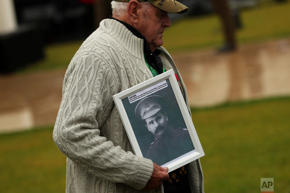 A descendant holds a portrait of an Australian soldier who died during the World War I in Villers-Bretonneux, France, Nov. 11, 2018. (AP Photo/Francisco Seco)