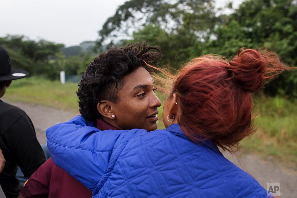 In this Nov. 2, 2018 photo, a couple who are part of a group of 50 or so LGBTQ migrants traveling with the migrant caravan hoping to reach the U.S. border, ride on the back of a flatbed truck as they make their way to Sayula, Mexico.  (AP Photo/Rodrigo Abd)