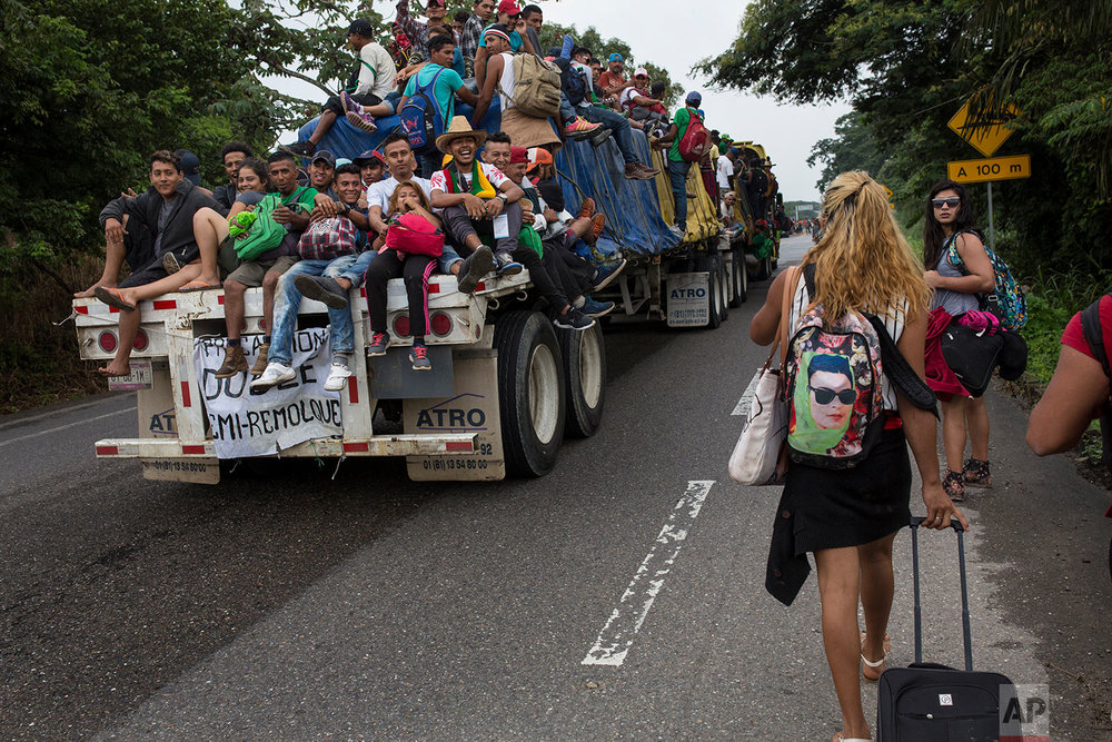 In this Nov. 2, 2018 photo, Central American migrants who hitched a ride on a flatbed truck jeer at members of about 50 LGBTQ migrants who are also part of the caravan hoping to reach the U.S. border, on the road to Donaji, Mexico. (AP Photo/Rodrigo Abd)