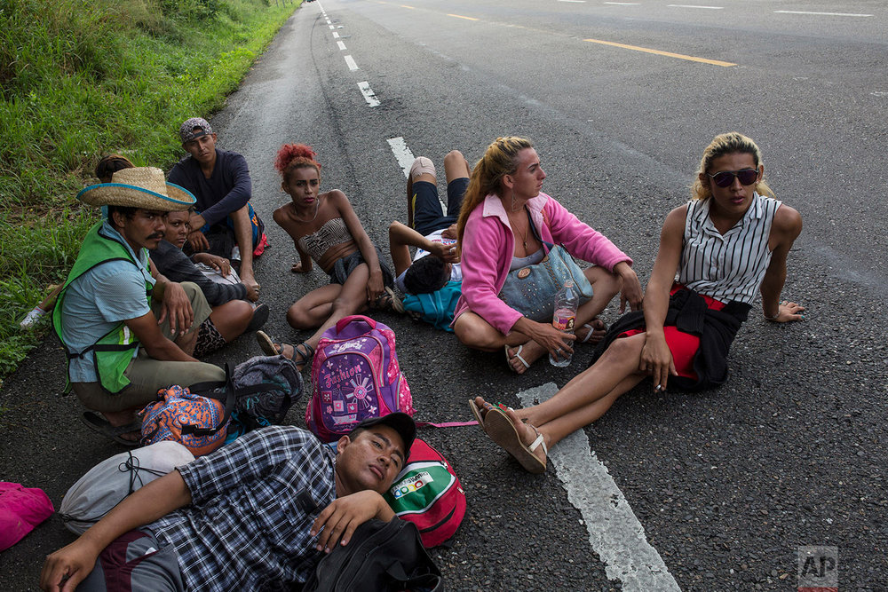 In this Nov. 2, 2018 photo, members of the LGBTQ community who are traveling with the Central American migrants caravan hoping to reach the U.S. border, wait on the side of the road for a ride to Donaji, Mexico. (AP Photo/Rodrigo Abd)