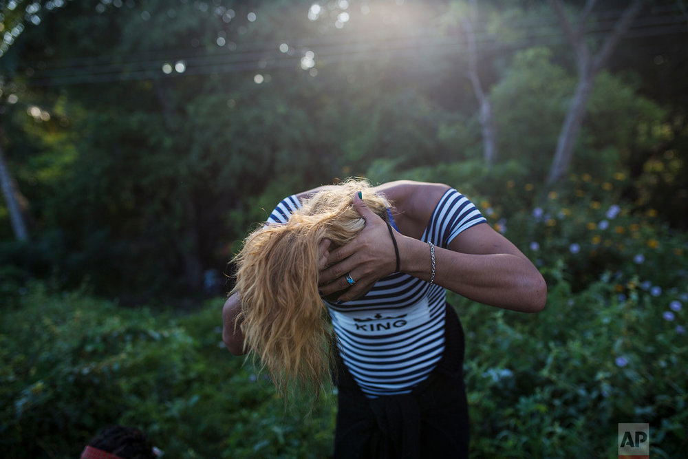 In this Nov. 2, 2018 photo, Honduran transgender Teresa Perez, who part of about 50 LGBTQ migrants traveling with the Central American migrants caravan hoping to reach the U.S. border, gathers her hair into a ponytail, on the outskirts of Donaji, Mexico. (AP Photo/Rodrigo Abd)