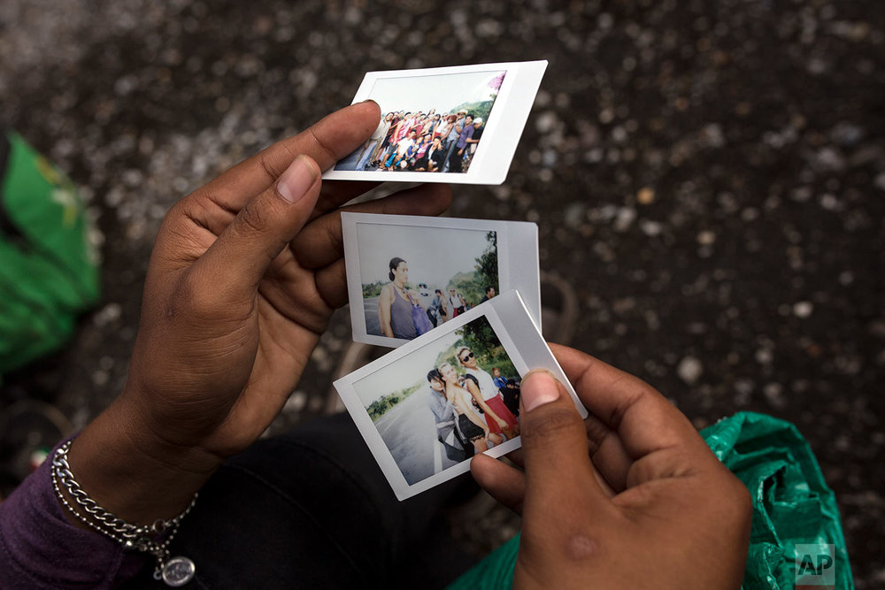 In this Nov. 3, 2018 photo, a member of a group of about 50 LGBTQ migrants traveling with the caravan hoping to reach the U.S. border, looks at polaroids taken by a colleague who is documenting their journey, on the road to Sayula, Mexico. (AP Photo/Rodrigo Abd)