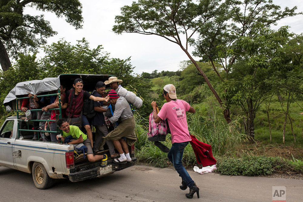 In this Nov. 2, 2018 photo, a member of about 50 LGBTQ migrants hoping to reach the U.S. border, chases after an overloaded pickup in hopes of hitching a ride to Donaji, Mexico. (AP Photo/Rodrigo Abd)