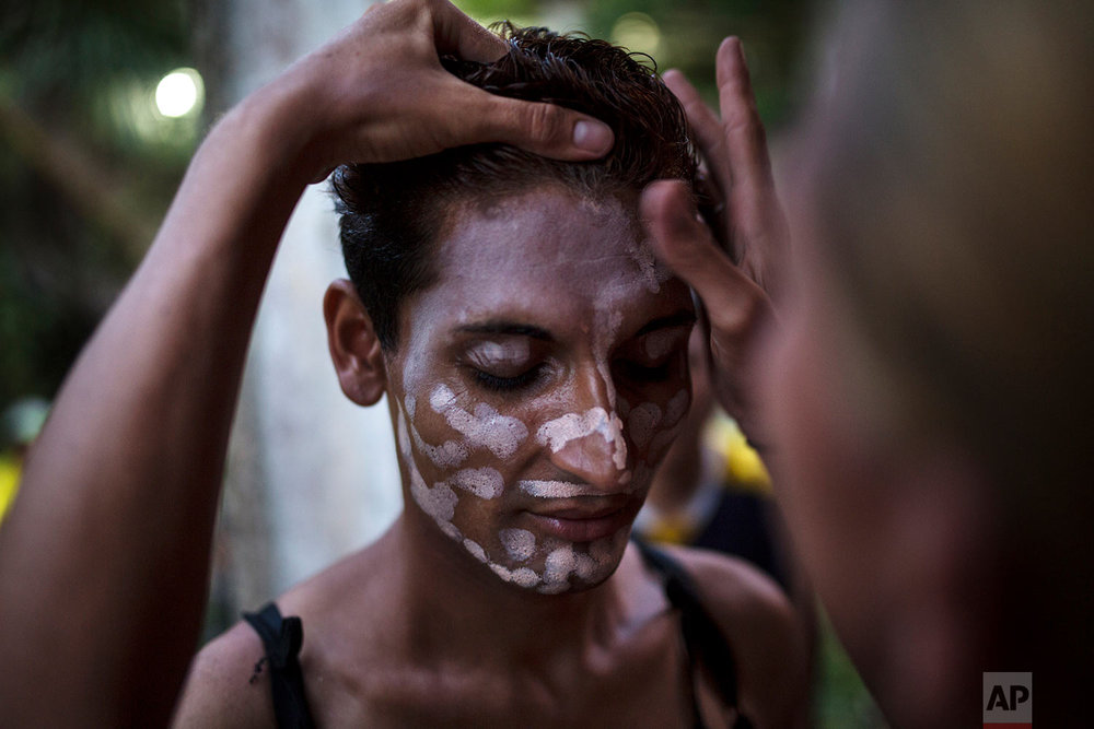 In this Nov. 1, 2018 photo, Honduran transgender Junior Castro, 22, who is part of the Central American migrants caravan hoping to reach the U.S. border, stands still as a friend applies foundation to her face, in Donaji, Mexico. (AP Photo/Rodrigo Abd)