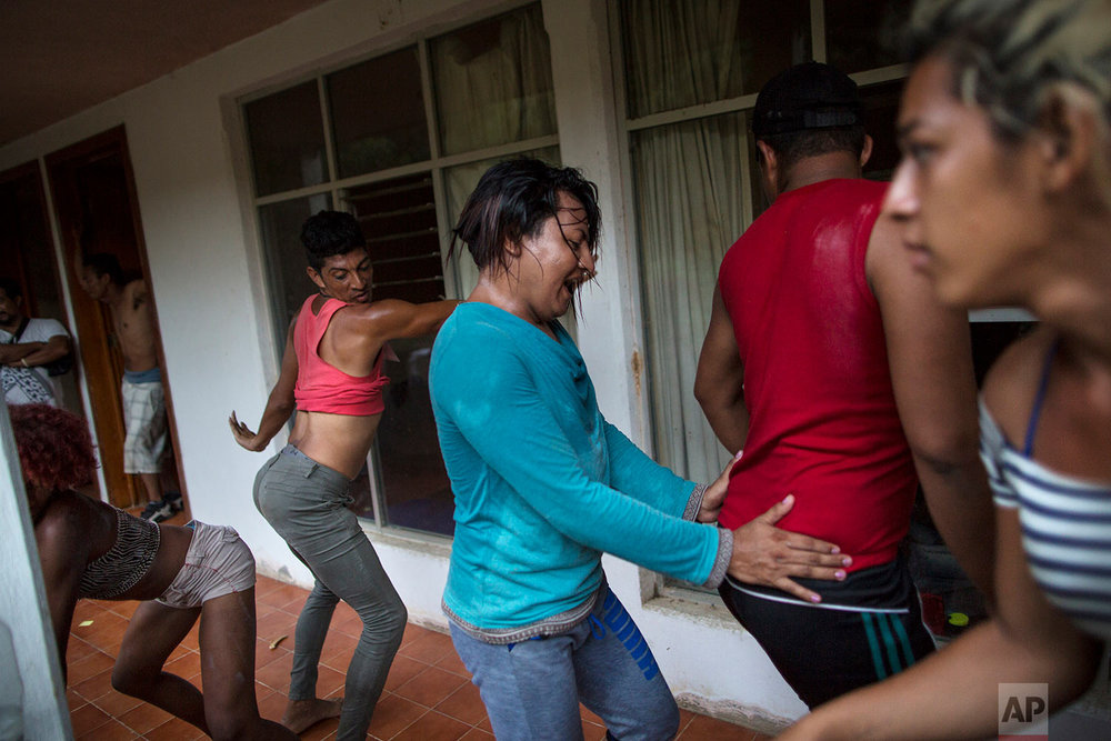 In this Nov. 1, 2018 photo, members of the LGBTQ community who are part of the Central American migrants caravan hoping to reach the U.S. border, break into a celebratory dance outside an abandoned hotel after arriving in Donaji, Mexico. (AP Photo/Rodrigo Abd)