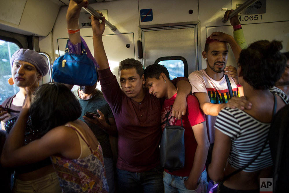 In this Nov. 8, 2018 photo, members of a group of 50 or so LGBTQ migrants traveling with the migrant caravan hoping to reach the U.S. border, ride the subway during a rest day, to the historic center in Mexico City. (AP Photo/Rodrigo Abd)