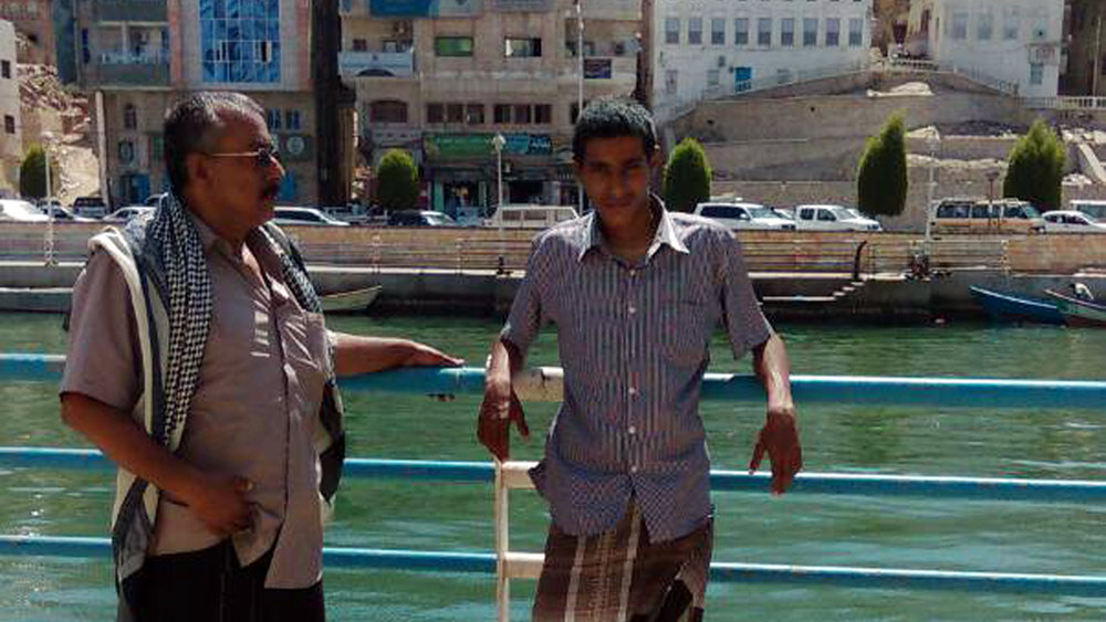 Abdullah, right, and his father pose for a photograph in the coastal city of Mukalla, Yemen. (Saleh family via AP)