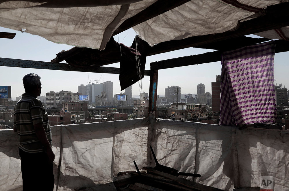 In this Oct. 28, 2018 photo, a man stands on the roof top of his home looking at the skyline littered with billboards promoting new residential suburban housing compounds, on the ring road, in Cairo, Egypt. (AP Photo/Nariman El-Mofty)