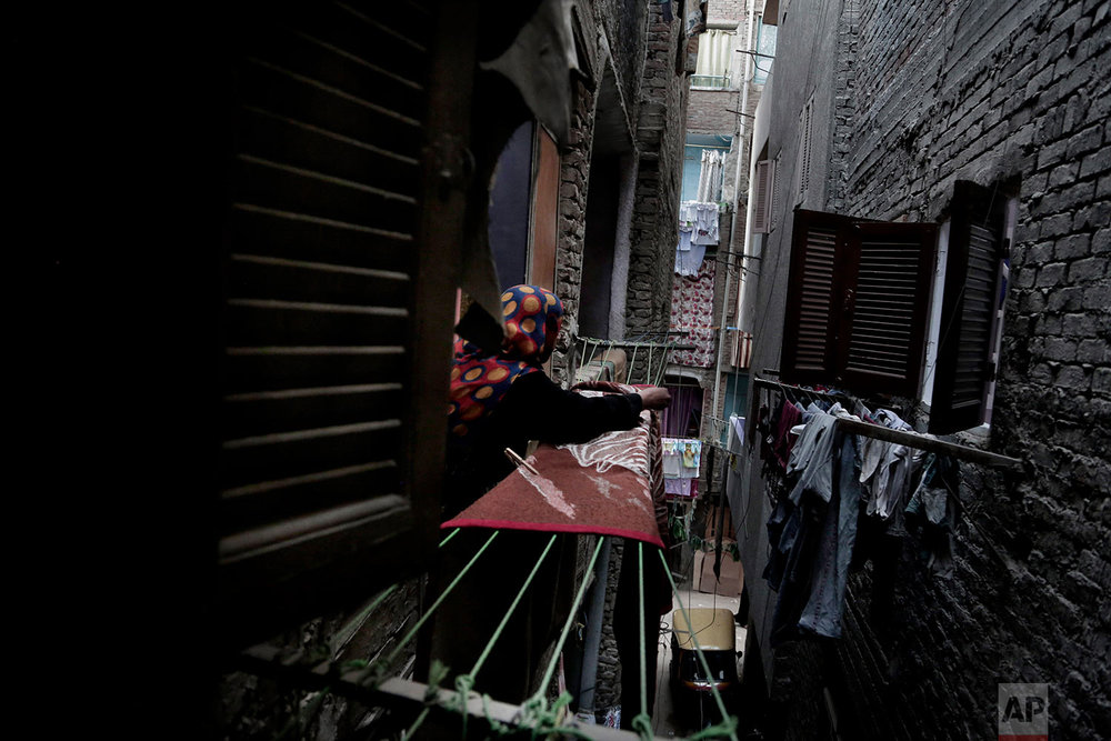 In this Oct. 29, 2018 photo, a woman hangs a rug in her home in the Imbaba neighborhood of Giza, Egypt. (AP Photo/Nariman El-Mofty)