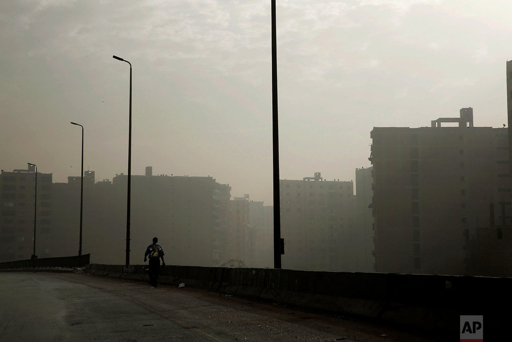 In this Oct. 23, 2018 photo, a man walks on the ring road on a foggy morning, in Cairo, Egypt. (AP Photo/Nariman El-Mofty)